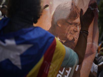 Un hombre sujeta una imagen del expresidente catalán Carles Puigdemont durante una protesta contra su detención frente al consulado italiano en Barcelona, este viernes.