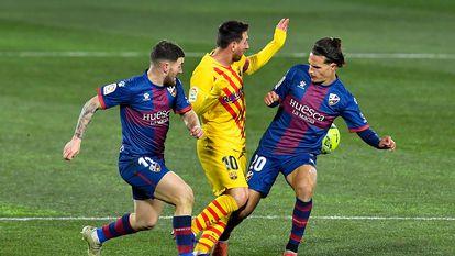 Messi, ante Javi Galán y Seoane en el duelo del Barcelona ante el Huesca.