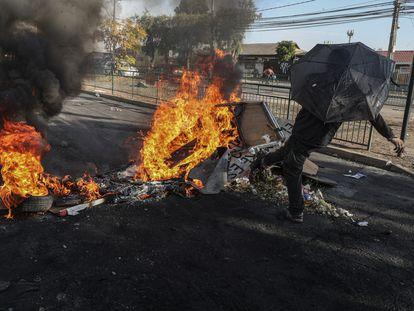 Un manifestante patea los escombros de una barricada en llamas durante una protesta en en el barrio de Cerrillos en Santiago, el viernes 22 de mayo.