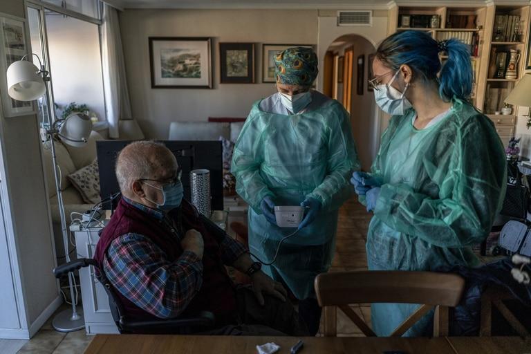 Las enfermeras Ana Fernández (con gorro) e Irene Ruiz, atienden a Eugenio Ramos, un enfermo crónico.