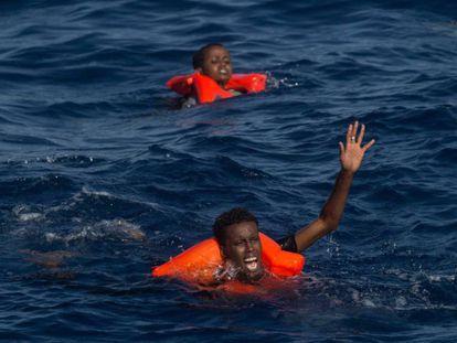 Dos náufragos subsaharianos piden auxilio tras zozobrar su embarcación cerca de la costa de Libia. / C. MCGRATH (GETTY IMAGES)
