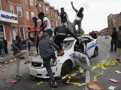 Manifestantes de Baltimore destrozan un coche policial.