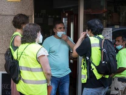 Un  equipo de informadores piden a un comerciante que guarde las medidas de seguridad.