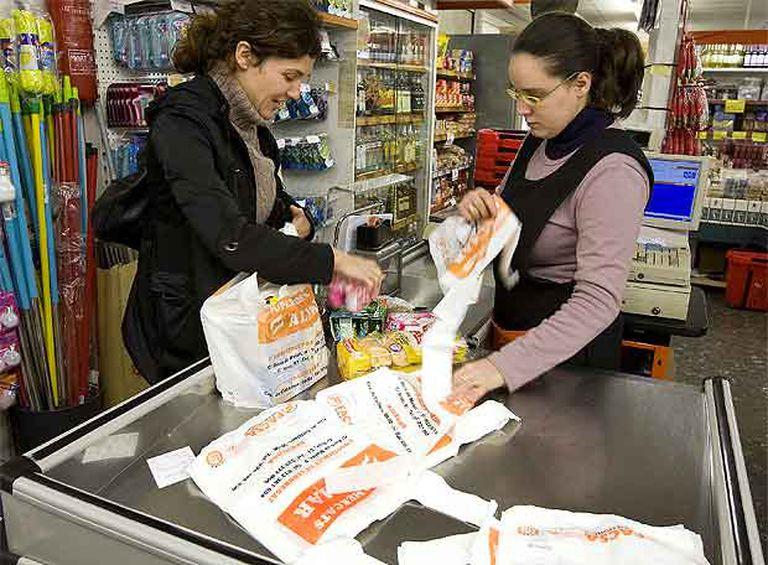 Una clienta y una cajera en un supermercado de L'Hospitalet de Llobregat metiendo la compra en bolsas de plástico, ayer.