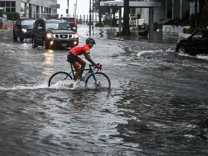 Un ciclista pasa por una calle inundada en Miami este lunes en medio de una intensa lluvia con viento por la tormenta Eta.