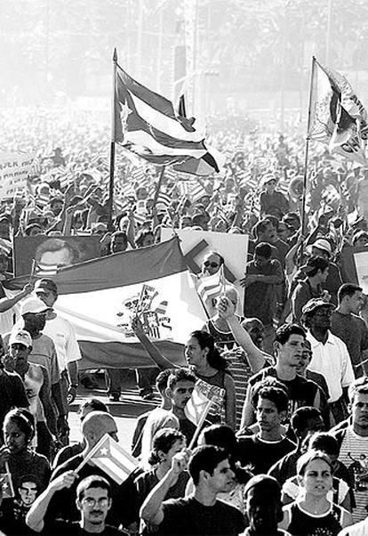 Manifestantes cubanos contra EE UU portan una bandera española en La Habana en mayo de 2004.