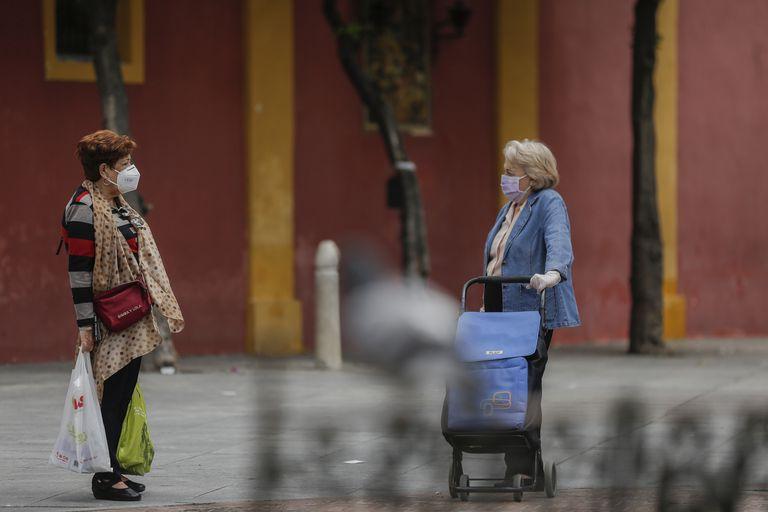 Dos personas conversan a distancia durante el quinto de la Fase 1 del plan de desescalada en Sevilla.