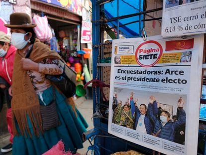 Una mujer camina en La Paz delante de la portada de un diario que anuncia el triunfo de Luis Arce en las elecciones del pasado domingo.