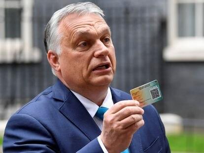 El primer ministro húngaro, Viktor Orban, muestra su tarjeta de vacunación tras reunirse el 28 de mayo en Londres con el primer ministro británico, Boris Johnson.