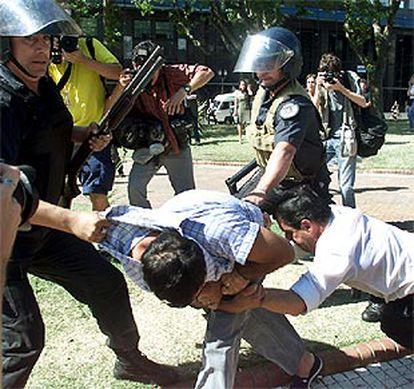 La policía, que ha cargado a caballo contra los manifestantes, detiene a un hombre ante la Casa Rosada.