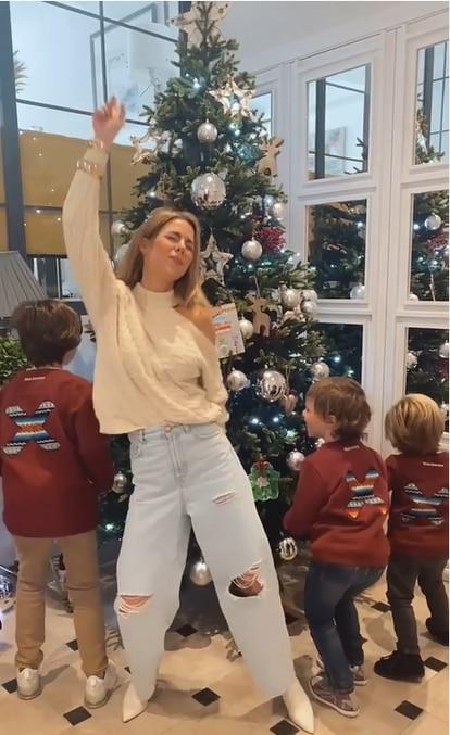 Amelia Bono y sus hijos bailando con el árbol de Navidad.