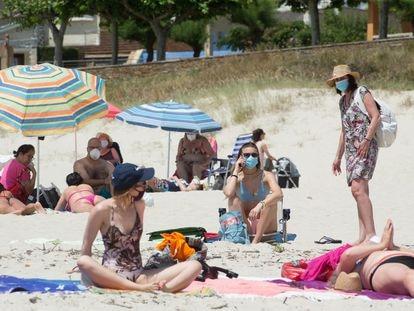 Varias personas protegidas con mascarillas toman el sol en la playa de A Rapadoira, en Foz, en la comarca de A Mariña, Lugo, este jueves.