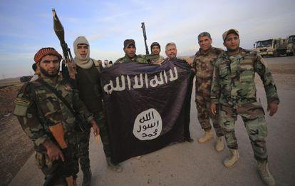 Combatientes iraquíes chiíes posan con una bandera arrebatada al EI.