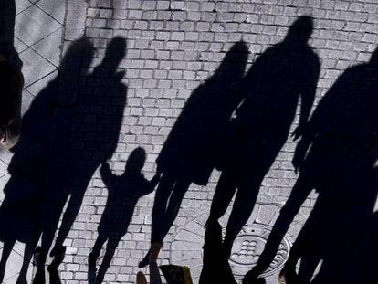 La sombra de un menor y varios adultos en una calle de Sevilla.