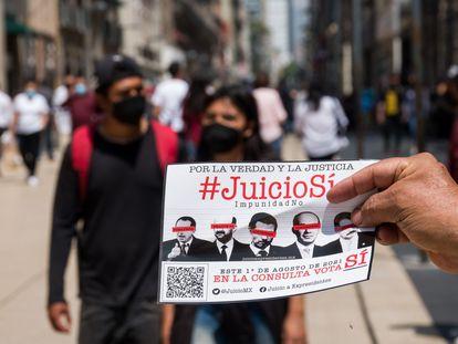 Un hombre entrega propaganda sobre la consulta para enjuiciar a los expresidentes en el centro de Ciudad de México, el 4 de julio.