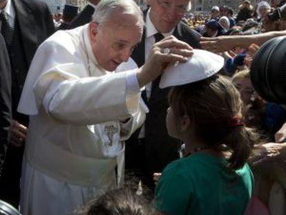 El papa Francisco en un gesto de complicidad con una niña.