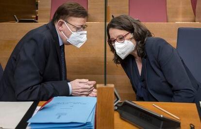 El presidente de la Generalitat, Ximo Puig, conversa con la vicepresidenta, Mónica Oltra, al inicio de la sesión de control en Les Corts de ayer.