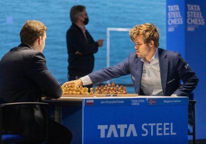 Carlsen pone en marcha el reloj de Duda al inicio de la partida de hoy; al fondo, el director del torneo, Jeroen Van den Berg