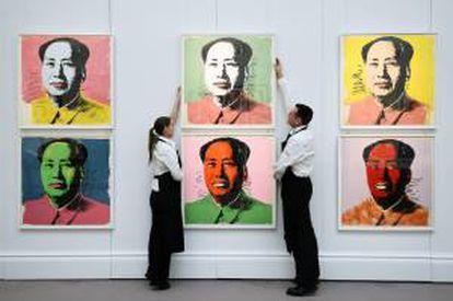 Dos trabajadores colocan varias obras de arte del artista Andy Warhol en las que se retrata al revolucionario comunista chino Mao, en la casa de subastas Sotheby's, Londres, Reino Unido.