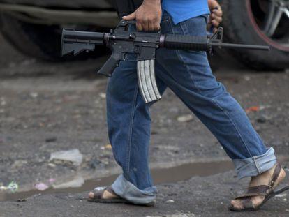 Un hombre del Consejo de Autodefensa de Michoacán con un fusil automático