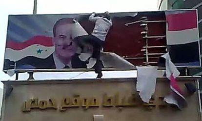 Un hombre destroza un cartel con la imagen del presidente El Asad en la ciudad deHoms, al norte de Damasco.