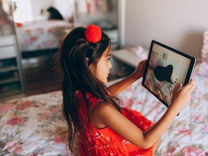 Una niña mira a su perro a través de una tableta.