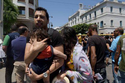Un hombre protege a un niño en el centro de Túnez tras el atentado en la calle Charles de Gaulle este jueves.