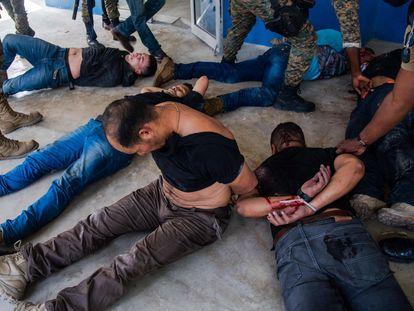 Policías custodian a un grupo de sospechosos de haber participado en el asesinato del presidente haitiano, Jovenel Moise, en Puerto Príncipe (Haití).