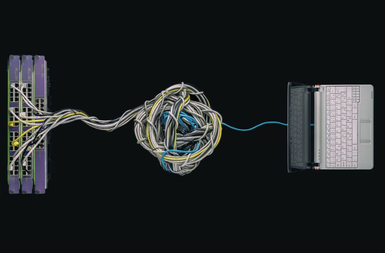 Un portátil conectado a una maraña de cables de red.