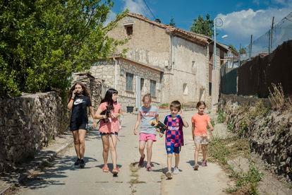 Cinco niños de Griegos pasean por las calles del pueblo.