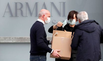 Trabajadores reparten mascarillas en el exterior del teatro donde el diseñador Giorgio Armani tenía previsto realizar su desfile en Milán, este domingo.