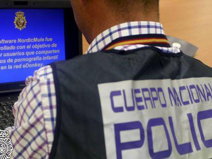 Un agente revisa un ordenador en una operación contra la pornografía infantil.