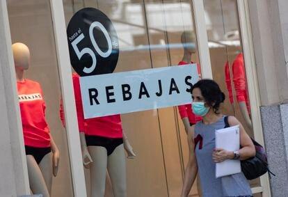 Una mujer pasa el viernes pasado frente a un escaparate de una tienda con carteles de descuentos.