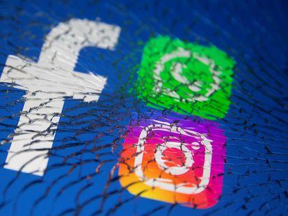 Los logos de Facebook, Whatsapp e Instagram, vistos a través de un cristal roto.