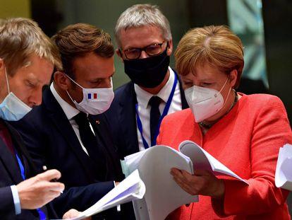Pedro Sánchez, Emmanuel Macron, y Angela Merkel examinan documentos durante la cumbre de la UE en Bruselas.