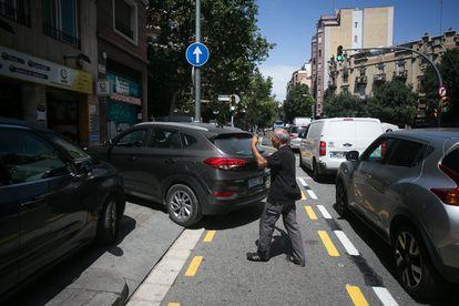 Dídac, mecánico de un taller de la calle de València de Barcelona, ayuda a maniobrar a un cliente sobre el nuevo carril bici.