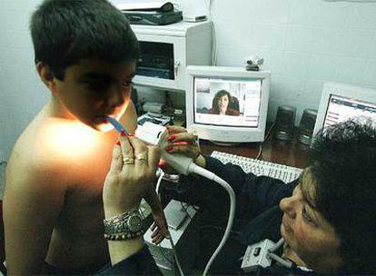 Una pediatra (en el monitor)  indica cómo  examinar a un niño durante un  ensayo de teleasistencia.