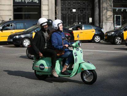 Usuarios de motos de alquiler por minutos de la empresa YeGo circula por la Via Laietana de Barcelona.