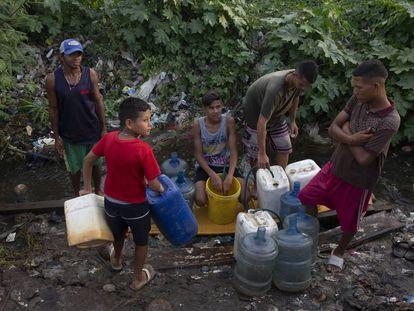 Un grupo de jóvenes se abastece de agua en un riachuelo formado por una tubería rota, el pasado viernes en Maracaibo.