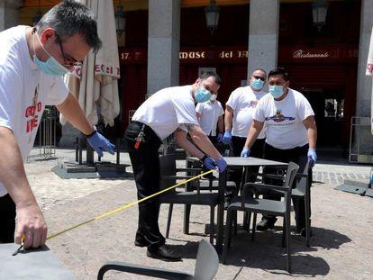 Empleados de los bares de la Plaza Mayor de Madrid medían ayer la distancia entre las mesas ante la reapertura hoy con la fase 1.