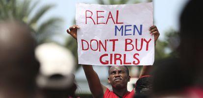 """Un hombre sostiene un cartel donde se lee """"los hombres de verdad no compran chicas"""" en una protesta en Lagos contra Boko Haram."""