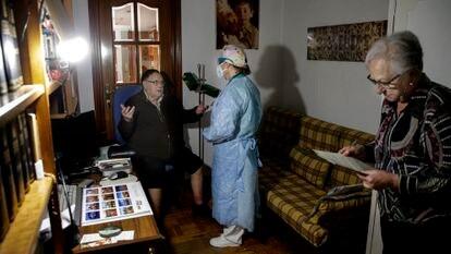 Una doctora atiende a un paciente en su domicilio de Madrid, el pasado abril.