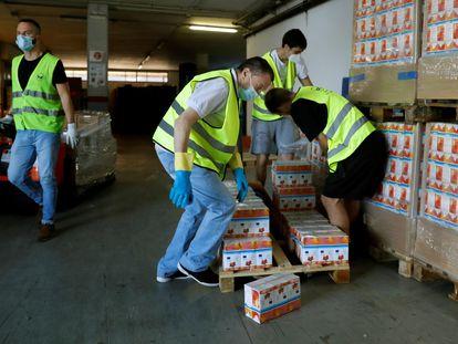 Voluntarios del Banco de Alimentos trabajan en el almacén de la organización en Barcelona.