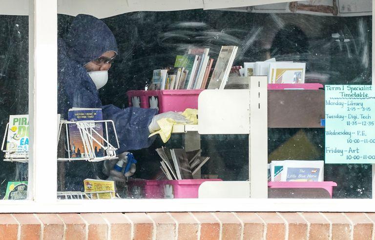 Un trabajador limpia una clase en una escuela en Melbourne, este domingo.