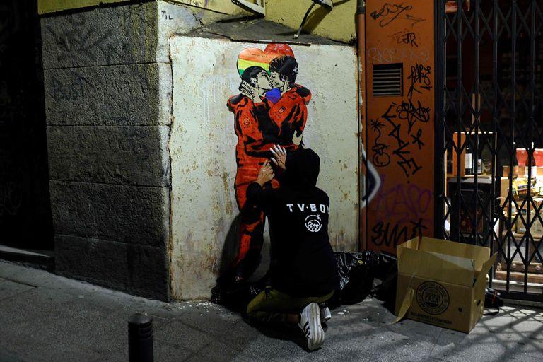 El artista TVBoy pinta el beso entre Tokio y Nairobi de 'La Casa de Papel' en el barrio de Chueca de Madrid.
