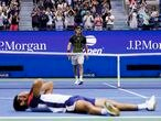Stefanos Tsitsipas, top, of Greece, walks to the net after loosing to Carlos Alcaraz, of Spain, during the third round of the US Open tennis championships, Friday, Sept. 3, 2021, in New York. (AP Photo/Frank Franklin II)