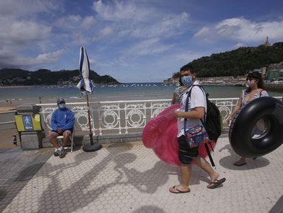 Unos jóvenes con mascarilla pasan ante el punto de control de aforo de la playa de La Concha en San Sebastián.