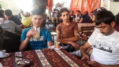 El traficante sirio Abu Nur, a la derecha, un intermediario y Hamzi, durante las negociaciones para pasar en patera a Grecia.