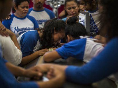 Amigos de Gerald Vázquez lloran sobre su ataúd durante su funeral.