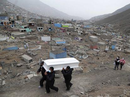 Los trabajadores del cementerio Mártires 19 de Julio, a las afueras de Lima, trasladan un ataúd.